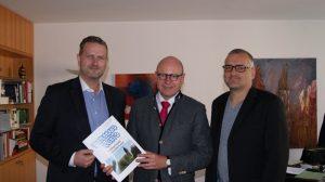 Marc Weßeling (links) und Heiko Philippski (rechts) übergeben eine Ausgabe ihrer Broschüre an Oberbürgermeister Markus Lewe (mitte).