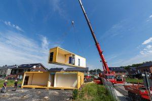 Ein Autokran hievt die Pavillons an ihren Standort an den Holunderweg. Dort finden zwei Kita-Gruppen Platz, ehe es ab 2021 in den Neubau in Sprakel-Ost geht. Foto: Presseamt  Münster.