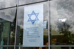 Das Banner mit dem Zitat der Bundeskanzlerin und dem Davidstern ist in der Glasfassade der Bezirksregierung am Domplatz zu sehen. © Bezirksregierung Münster.